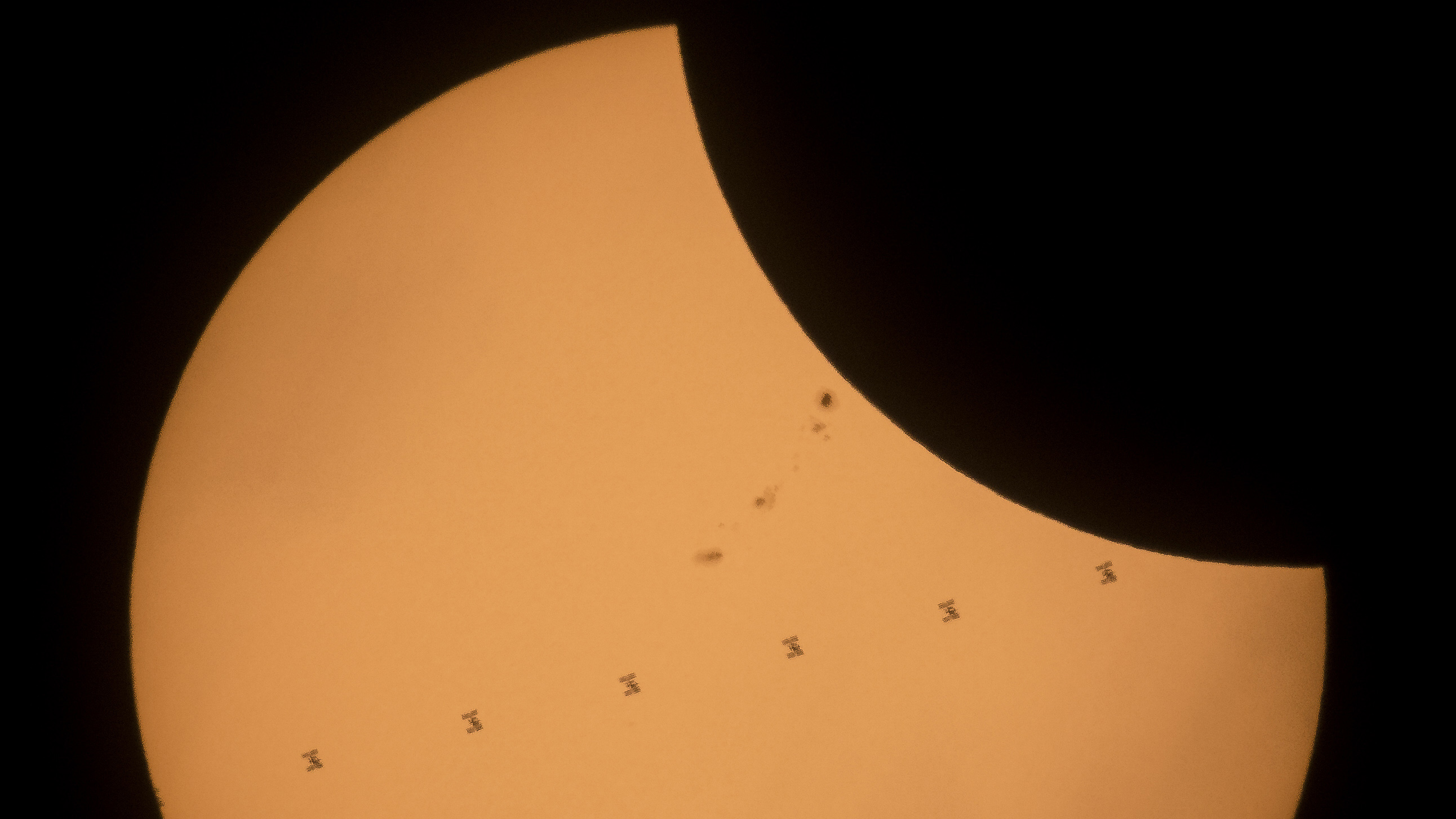 This composite image, made from seven frames, shows the International Space Station, with a crew of six onboard, as it transits the Sun at roughly five miles per second during a partial solar eclipse, Monday, Aug. 21, 2017 near Banner, Wyoming. Onboard as part of Expedition 52 are: NASA astronauts Peggy Whitson, Jack Fischer, and Randy Bresnik; Russian cosmonauts Fyodor Yurchikhin and Sergey Ryazanskiy; and ESA (European Space Agency) astronaut Paolo Nespoli. A total solar eclipse swept across a narrow portion of the contiguous United States from Lincoln Beach, Oregon to Charleston, South Carolina. A partial solar eclipse was visible across the entire North American continent along with parts of South America, Africa, and Europe.  Photo Credit: (NASA/Joel Kowsky)